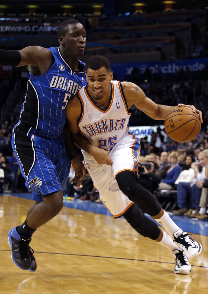 Photo - Oklahoma City's Thabo Sefolosha (25) drives to the basket as he is guarded by Orlando's Victor Oladipo (5) during the NBA basketball game between the Oklahoma City Thunder and the Orlando Magic at the Chesapeake Energy Arena, Sunday, Dec. 15,  2013. Photo by Sarah Phipps, The Oklahoman