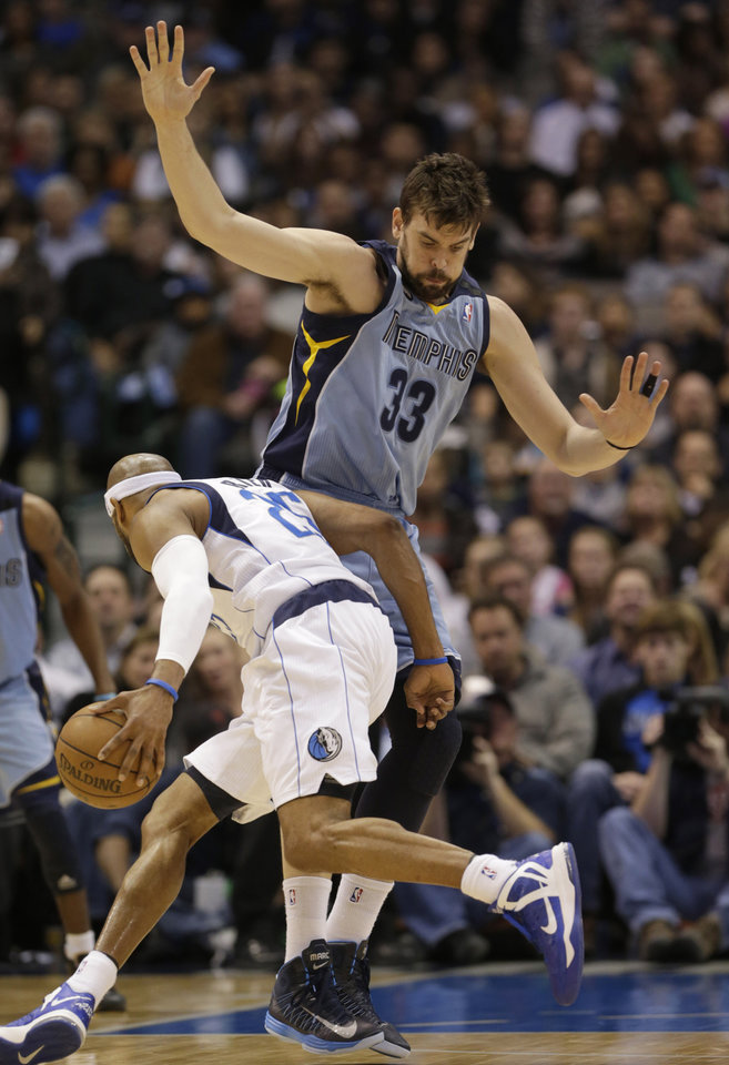 Memphis Grizzlies center Marc Gasol (33), of Spain, defends against driving Dallas Mavericks shooting guard Vince Carter (25) during the first half of an NBA basketball game on Saturday, Jan. 12, 2013, in Dallas. (AP Photo/LM Otero)