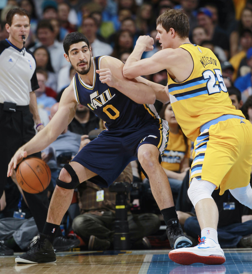 Photo - Utah Jazz center Enes Kanter, left, of Turkey, works ball inside as Denver Nuggets center Timofey Mozgov, of Russia, covers in the first quarter of an NBA basketball game in Denver on Saturday, April 12, 2014. (AP Photo/David Zalubowski)