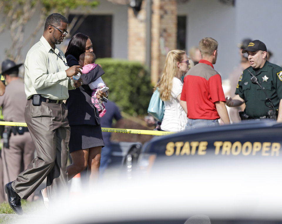 Photo - Parents leave a day care center with their children after a vehicle crashed into the center, Wednesday, April 9, 2014, in Winter Park, Fla. At least 15 people were injured, including children. (AP Photo/John Raoux)