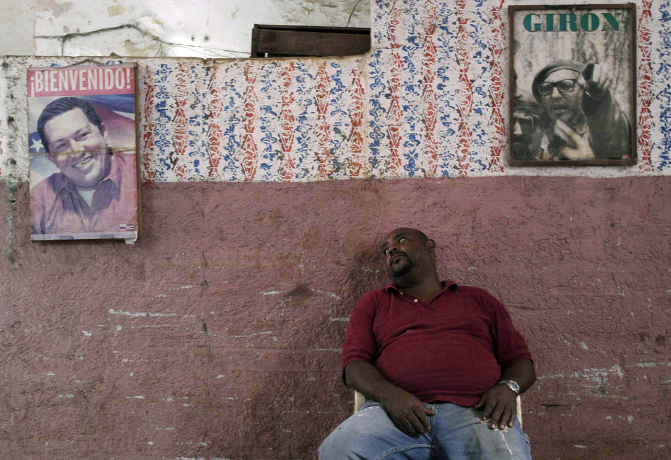 Photo - FILE - In this Dec. 10, 2012 file photo, a worker who sells vegetables takes a rest against a wall featuring posters of Venezuela's President Hugo Chavez, left, and former Cuban leader Fidel Castro, in Havana, Cuba.  Cuba's state TV cut from a nightly soap opera to the televised speech on Dec. 8, 2012, where Chavez revealed that his cancer had returned for a second time; facing his fourth cancer surgery in 18 months. The news shocked not only Venezuelans but millions of Cubans who have come to depend on Chavez's largesse for everything from subsidized oil to cheap loans. (AP Photo/Franklin Reyes, File)