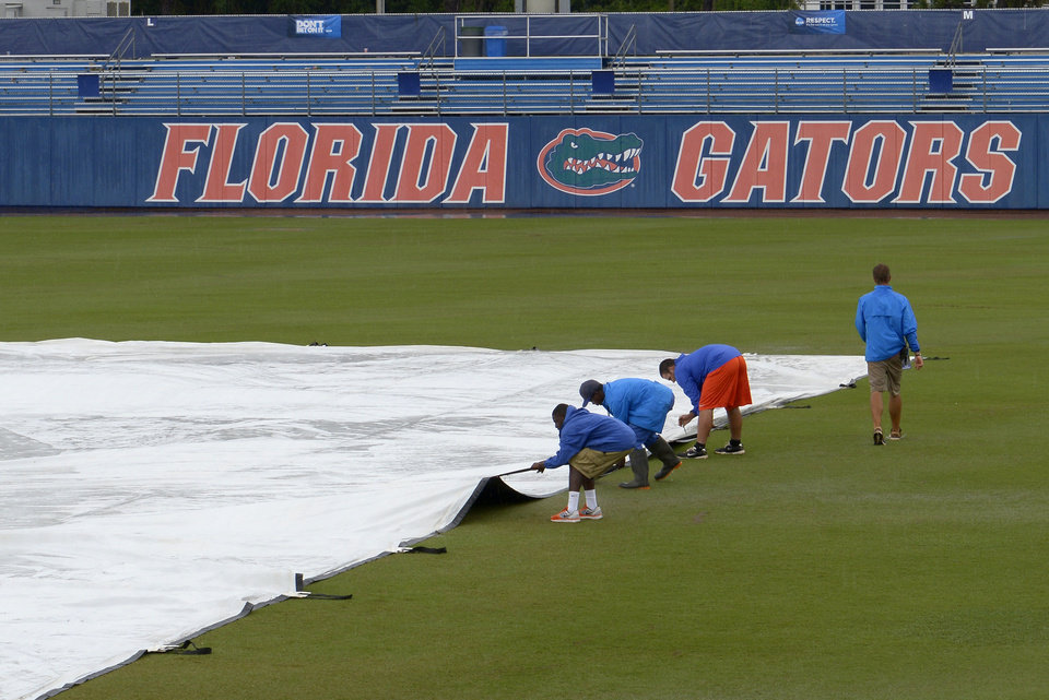 Photo - Members of the grounds crew tend to the field during a rain delay in the third inning of an NCAA college baseball regional tournament game between Florida and North Carolina in Gainesville, Fla., Saturday, May 31, 2014.(AP Photo/Phelan M. Ebenhack)