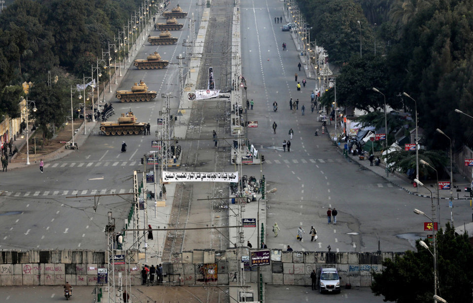 "Military tanks deployed in front of the presidential palace in Cairo, Egypt, Sunday, Dec. 16, 2012. Key Egyptian rights groups called Sunday for a repeat of the first round of the constitutional referendum, alleging the vote was marred by widespread violations. Islamists who back the disputed charter claimed they were in the lead with a majority of ""yes"" votes. (AP Photo/Hassan Ammar)"