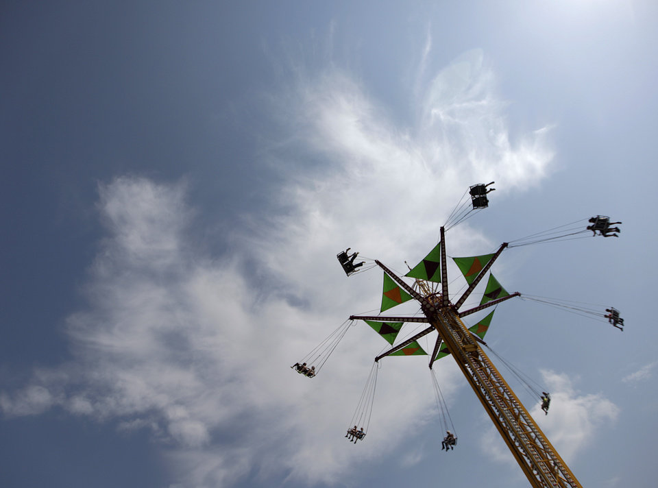 Fair-goers take a ride at the Oklahoma State Fair in Oklahoma City, Friday, Sept. 21, 2012.  Photo by Garett Fisbeck, The Oklahoman