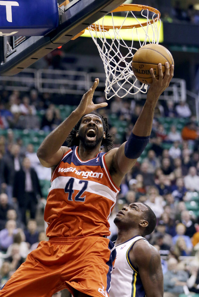 Washington Wizards' Nene (42) lays the ball up as Utah Jazz's Paul Millsap (24) defends during the first quarter of an NBA basketball game, Wednesday, Jan. 23, 2013, in Salt Lake City. (AP Photo/Rick Bowmer)