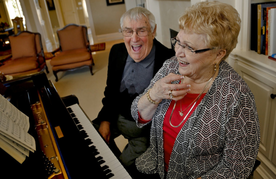 Photo - Bob Aldridge laughs with Mona Long as she plays the piano in Edmond, Okla. on Tuesday, Feb. 3, 2015. The two have written the book 'October Rose' that speaks of their late life romance together. Photo by Chris Landsberger, The Oklahoman   	L