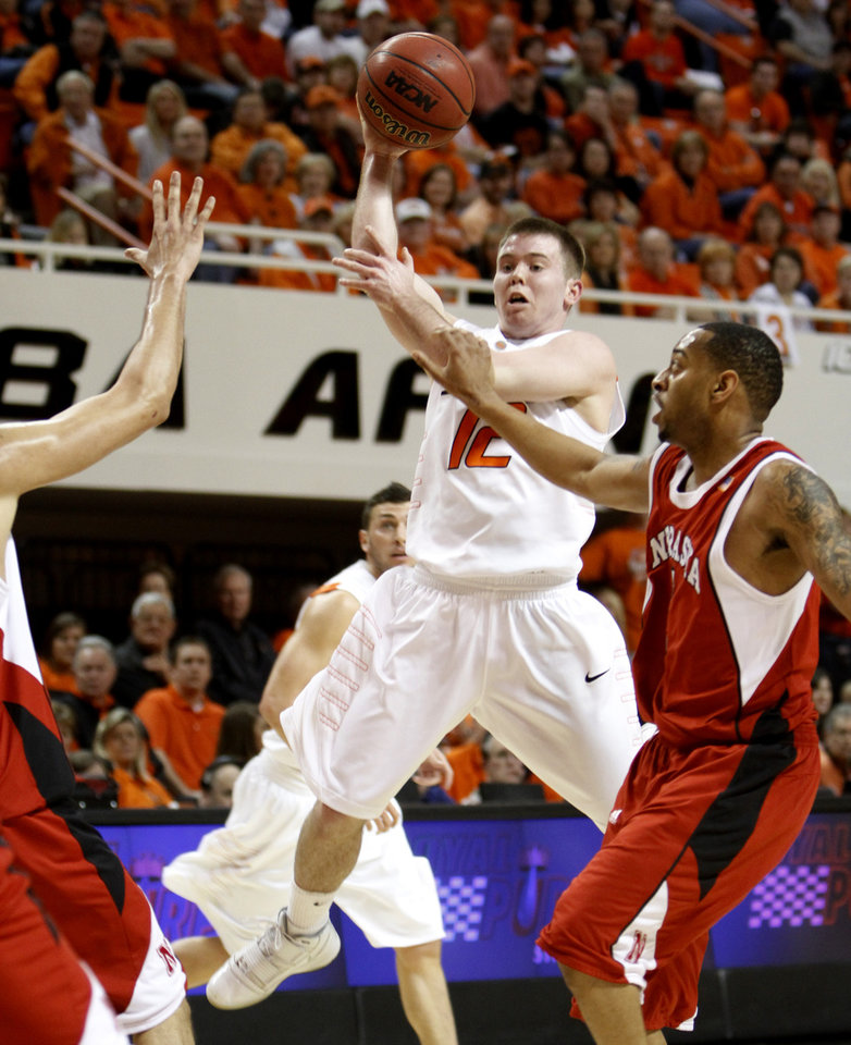 Photo - OSU's Keiton Page draws the defense as he dishes off during the college basketball game between Oklahoma State University and Nebraska at Gallagher-Iba Arena in Stillwater Saturday, March 6, 2010. Photo by Doug Hoke, The Oklahoman  ORG XMIT: KOD