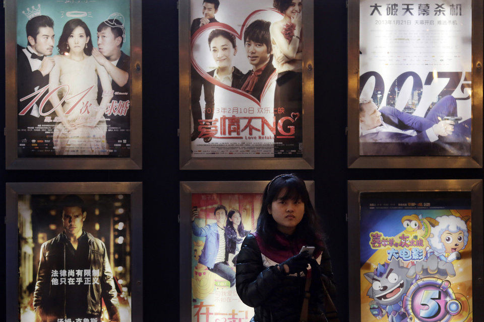 In this Wednesday Feb. 13, 2013 photo, a woman stands in front of the advertisements of Chinese and foreign films on showing at a movie theater in Shanghai, China. Tens of millions of film fanatics are entering theaters around Asia during the long Lunar New Year holiday, but Hollywood can�t count on them to boost the box office for its mostly serious Oscar nominees. Even with the Academy Awards buzz at a peak barely two weeks before the ceremony, patrons are opting for lighter fare. (AP Photo/Eugene Hoshiko)