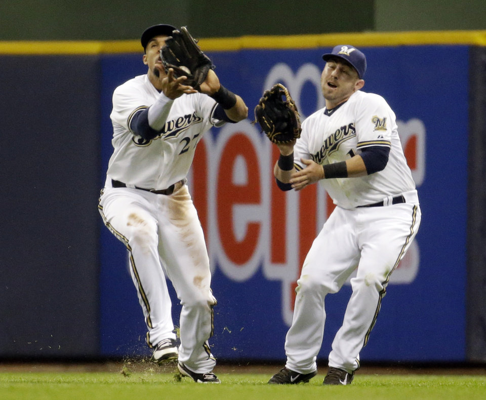 Photo - Milwaukee Brewers' Carlos Gomez, left, and Caleb Gindl nearly collide as Gomez catches a ball hit by Arizona Diamondbacks' Martin Prado during the sixth inning of a baseball game Monday, May 5, 2014, in Milwaukee. (AP Photo/Morry Gash)