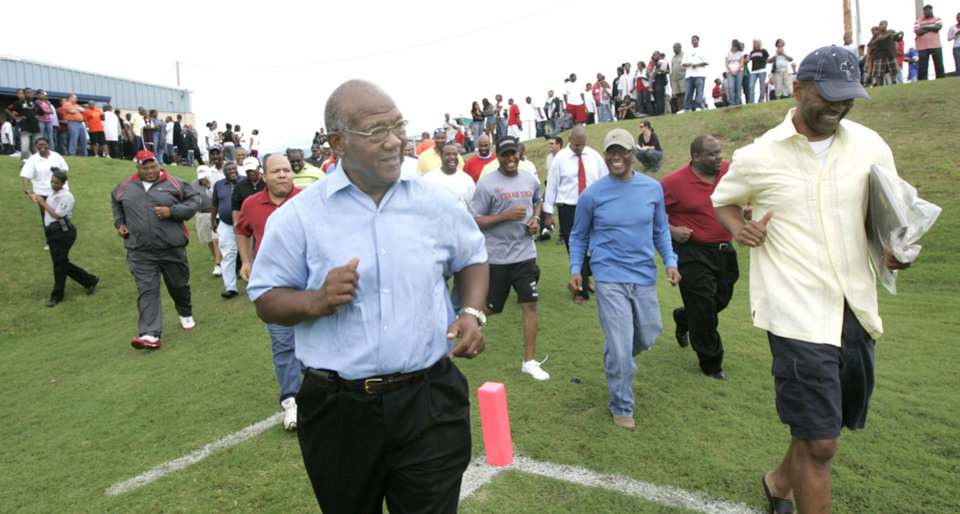 Photo - HIGH SCHOOL FOOTBALL / NAME: Former Millwood head coach Leodies Robinson runs out onto the field during a halftime ceremony naming the football field after the legendary coach at Millwood High school in Oklahoma City, Oklahoma September 12, 2009. Photo by Steve Gooch, The Oklahoman ORG XMIT: KOD