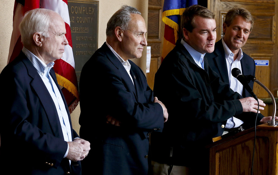 Photo - Sen. Michael Bennett, D-Colo. second right, speaks, as, from left, Sen. John McCain, R-Ariz., Sen. Chuck Schumer, D-N.Y., and Sen. Jeff Flake, R-Ariz., listen during a news conference after their tour of the Mexico border with the United States on Wednesday, March 27, 2013, in Nogales, Ariz. The senators are part of a larger group of legislators shaping and negotiating details of an immigration reform package vowed Wednesday to make the legislation public when Congress reconvenes next month. (AP Photo/Ross D. Franklin)