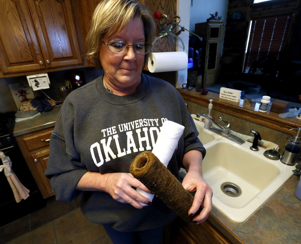 Photo - Jeannie Salmon changes her well's pre-filter at least monthly and sometimes weekly as she struggles with water issues at her rural home Thursday in Lexington. Photo by Steve Sisney, The Oklahoman  STEVE SISNEY
