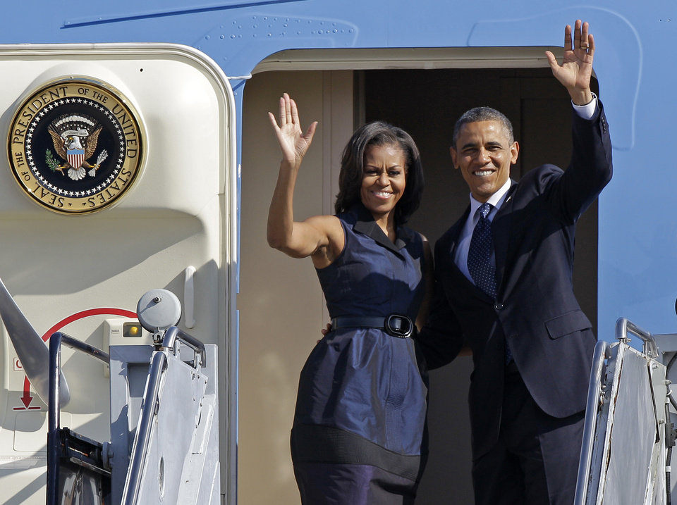 Photo -   President Barack Obama and first lady Michelle Obama wave as they board Air Force One before leaving Charlotte, N.C., after the Democratic National Convention, Friday, Sept. 7, 2012. (AP Photo/Chuck Burton)