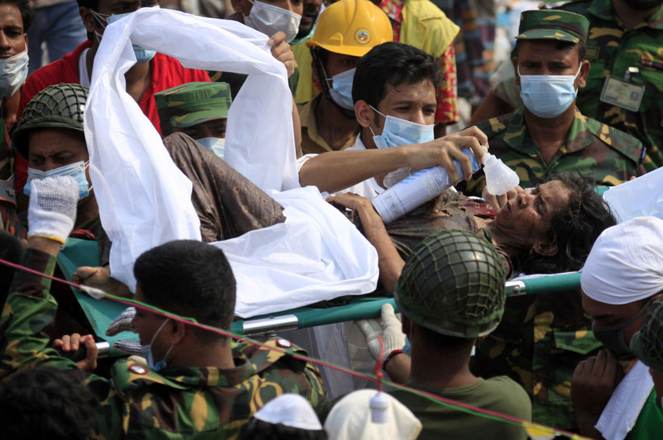 Photo - A survivor is given oxygen as she was evacuated from a garment factory building that collapsed Wednesday in Savar, near Dhaka, Bangladesh, Saturday, April 27, 2013. Police in Bangladesh took five people into custody in connection with the collapse of a shoddily-constructed building this week, as rescue workers pulled 19 survivors out of the rubble on Saturday and vowed to continue as long as necessary to find others despite fading hopes.(AP Photo/Wong Maye-E)