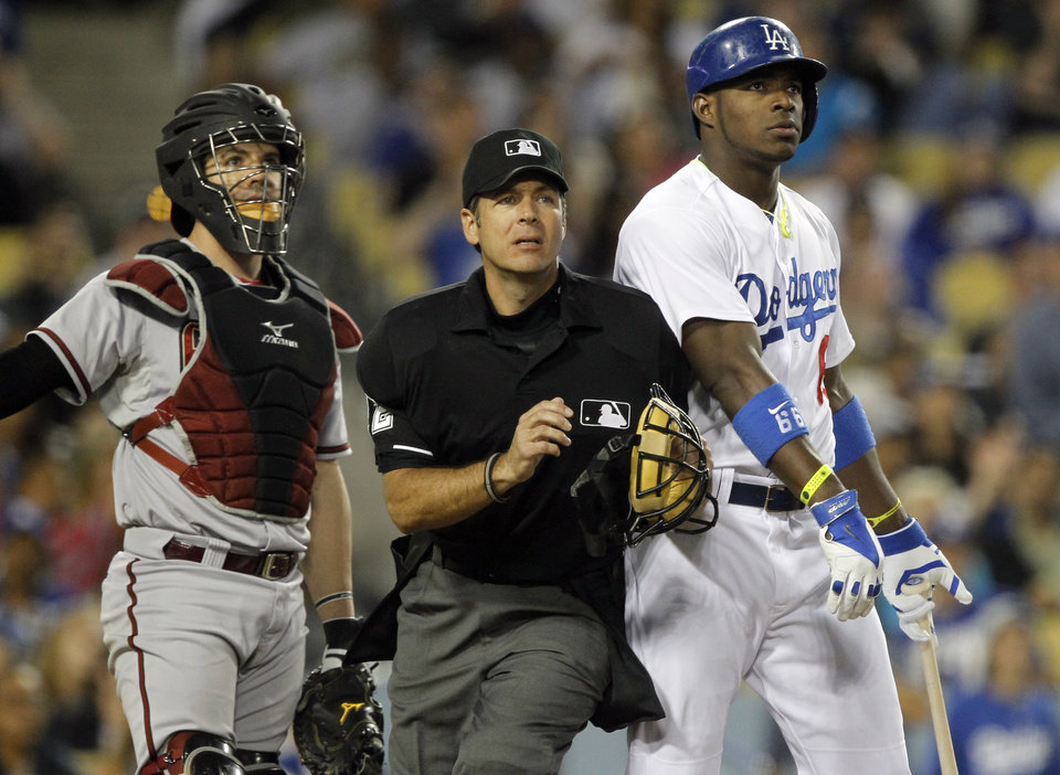 Photo - Home plate umpire James Hoye, center, bumps into Los Angeles Dodgers' Yasiel Puig, right, to call a foul ball with Arizona Diamondbacks catcher Tuffy Gosewisch, left, in the third inning of a baseball game on Friday, June 13, 2014, in Los Angeles. (AP Photo/Alex Gallardo)