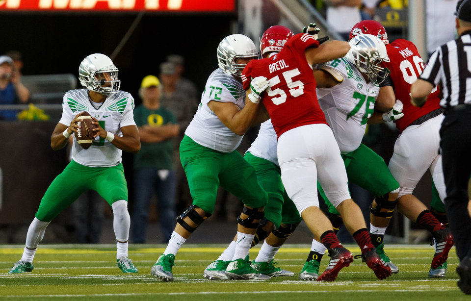 Photo - Oregon quarterback Marcus Mariota (8) looks for an open receiver during the first quarter against South Dakota in an NCAA college football game in Eugene, Ore., Saturday, Aug. 30, 2014. (AP Photo/Ryan Kang)