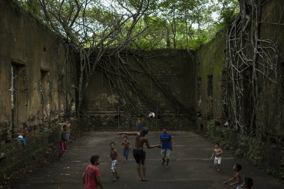 Photo - In this May 21, 2014 photo, Children and adults play soccer in the ruins of Paricatuba, near Manaus, Brazil. The haunting ruins built in 1898 at the height of the region's rubber boom, briefly transformed Manaus into one of the richest cities in the world. The sprawling villa was initially intended to house the Italian immigrants who arrived to work in the rubber trade. The building's decline over the next century mirrored that of Manaus, which after the rubber boom went bust, slipped into a long period of decadence and decay. (AP Photo/Felipe Dana)