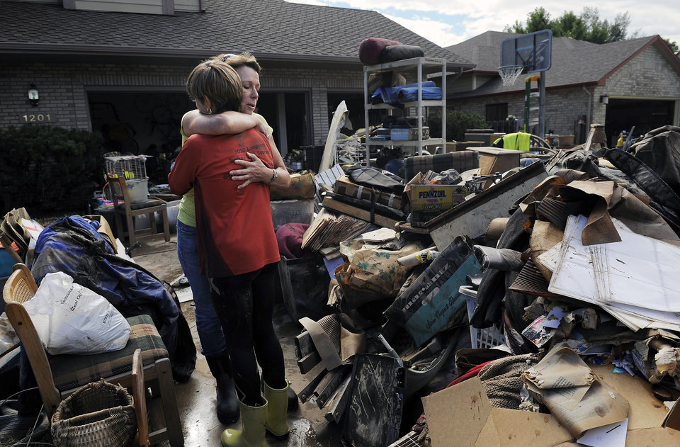 Photo - AP10ThingsToSee - Homeowner Chris Ringdahl, left, is comforted by friend Katherine MacIntosh in front of her possessions as they cleanup from the floodwaters in Longmont, Colo., on Monday, Sept. 16, 2013. (AP Photo/Chris Schneider, File)