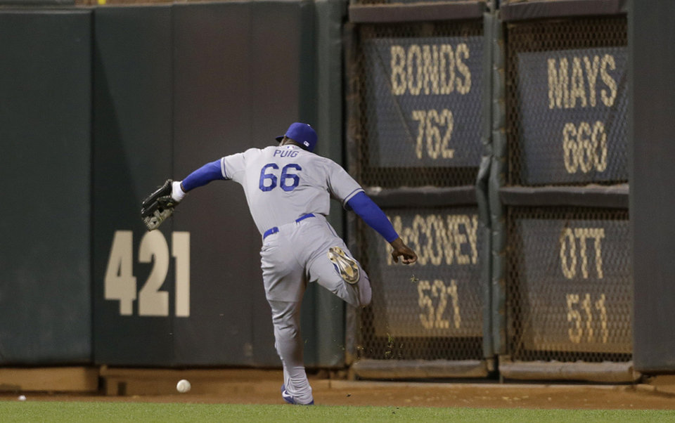 Photo - Los Angeles Dodgers right fielder Yasiel Puig cannot catch a three-run triple by San Francisco Giants' Tony Abreu during the second inning of a baseball game in San Francisco, Wednesday, Sept. 25, 2013. (AP Photo/Jeff Chiu)