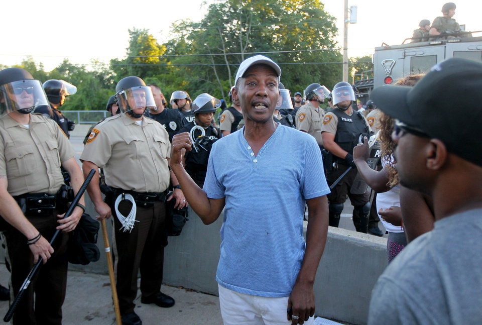 """Photo - """"I'm just ready to leave,"""" said Jeffrey Houston, of St. Louis, Wednesday, Aug. 13, 2014, in Ferguson, Mo. """"They're blocking the sidewalks. I don't want to be here."""" Police had created a line across the street and sidewalk in Ferguson. (AP Photo/St. Louis Post-Dispatch, David Carson)"""