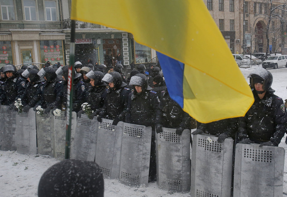Photo - A Ukrainian national flag is waved by pro-European protesters as Ukrainian riot police block the road next to Pro-European Union activists gathered on the Independence Square in Kiev, Ukraine, Monday, Dec. 9, 2013. The policemen, wearing helmets and holding shields, formed a chain across Kiev's main street outside the city building. Organizers called on protesters to vacate the city hall and the other building which the opposition had used as its headquarters.  (AP Photo/Sergei Grits)