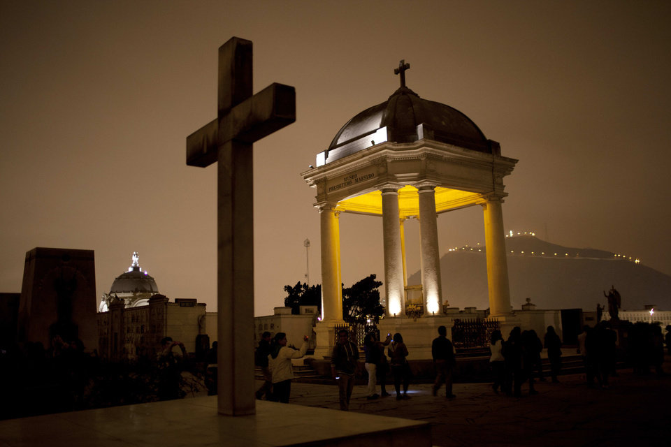 In this Dec. 6, 2012 photo, people take a nighttime guided tour through the Presbitero Matias Maestro cemetery in Lima, Peru. There are no more burials anymore, unless a family owns a mausoleum. (AP Photo/Rodrigo Abd)