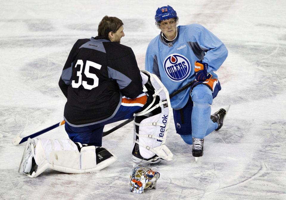 Photo - Edmonton Oilers goalie Nikolai Khabibulin, left, and Ales Hemsky talk during a break at their NHL hockey training camp in Edmonton, Alberta, Monday, Jan. 14, 2013. (AP Photo/The Canadian Press, Jason Franson)