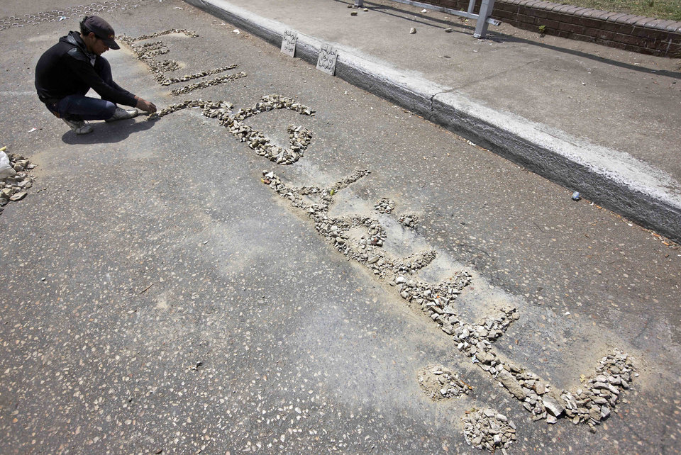 Photo -   An Egyptian protester arranges rocks to read in Arabic: