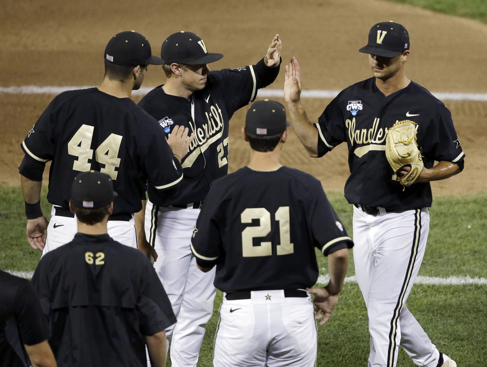 Photo - Vanderbilt pitcher Tyler Beede, right, leaves in the seventh inning of Game 2 of the best-of-three NCAA baseball College World Series finals against Virginia in Omaha, Neb., Tuesday, June 24, 2014. (AP Photo/Nati Harnik)