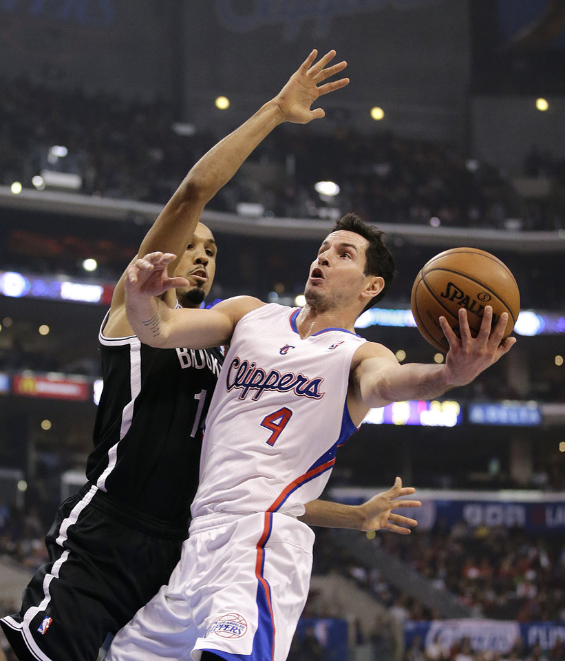 Photo - Los Angeles Clippers' J.J. Redick, right, goes up for a basket against Brooklyn Nets' Shaun Livingston during the first half of an NBA basketball game Saturday, Nov. 16, 2013, in Los Angeles. (AP Photo/Jae C. Hong)