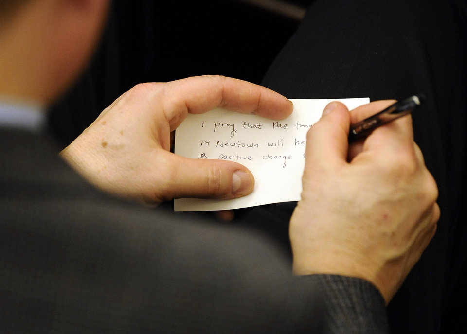 A man writes a prayer for Newtown on a note card during an interfaith sermon at Newtown Congregational Church in Newtown, Conn., Sunday, Jan. 20, 2013. Forbes, who led one of the country�s most prominent liberal Protestant churches,  is speaking in Newtown to honor the victims of last month�s school shooting and the legacy of the Rev. Martin Luther King Jr. (AP Photo/Jessica Hill)