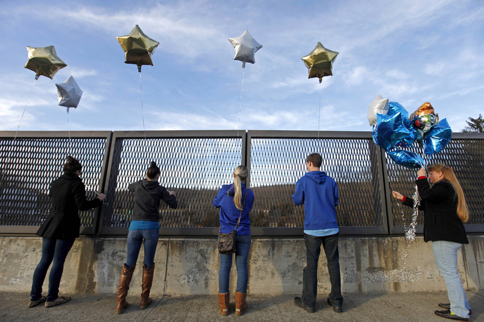 Photo - Suada Likovic, 24, from left, Chelsea Crain, 23, Kristin Hoyt, 18, Jeffrey Hoyt, 16, and Linda Hoyt, all of Danbury, Conn., tie balloons to an overpass up the road from the Sandy Hook Elementary School, Saturday, Dec. 15, 2012, in Newtown, Conn. The massacre of 26 children and adults at Sandy Hook Elementary school elicited horror and soul-searching around the world even as it raised more basic questions about why the gunman, 20-year-old Adam Lanza, would have been driven to such a crime and how he chose his victims. (AP Photo/David Goldman) ORG XMIT: CTDG121