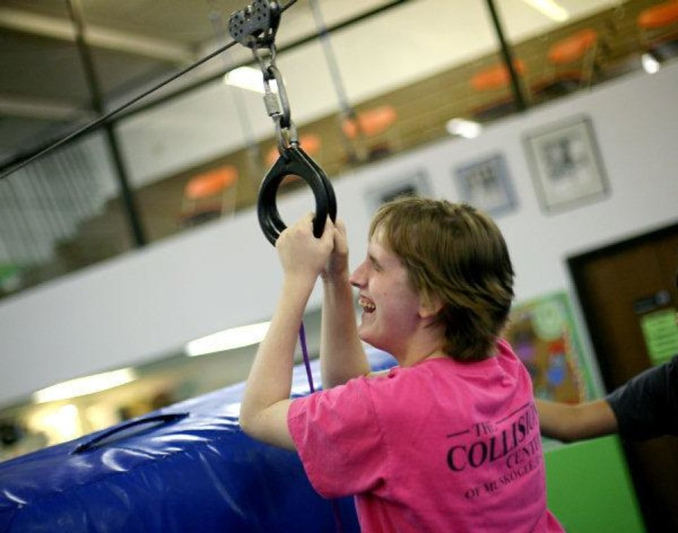 Brittany Donley, of Cache, laughs as she completes a zip line ride at Mat Trotters Gymnastics in Oklahoma City on Wednesday during the Oklahomans Without Limits summer camp for children who are blind or visually impaired. PHOTO BY JOHN CLANTON, THE OKLAHOMAN <strong>JOHN CLANTON - John Clanton</strong>