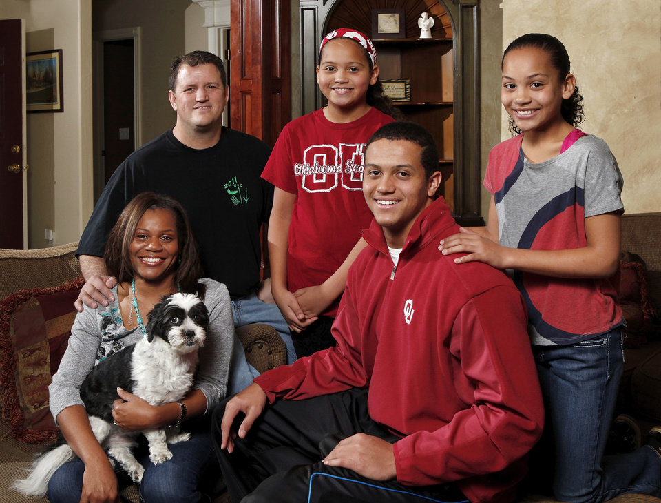Photo - Former OU football player Scott Evans, upper left, and wife, Tenika, pose for a portrait with their son, Jordan, 18, and daughters, Jessika, 11, and Jacie, 12, right.   Tenika holds family pet, Koda. The family was  photographed in their home in Norman on Saturday, Jan. 26, 2013.     Photo by Jim Beckel, The Oklahoman