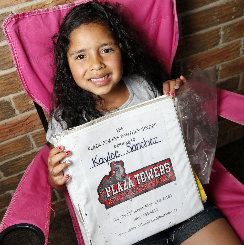 Photo - Kaylee Sanchez, 6, sits on her porch in the Plaza Towers neighborhood with her binder which was recovered from the rubble of Plaza Towers Elementary School in Moore. Photo by Nate Billings, The Oklahoman   NATE BILLINGS - NATE BILLINGS