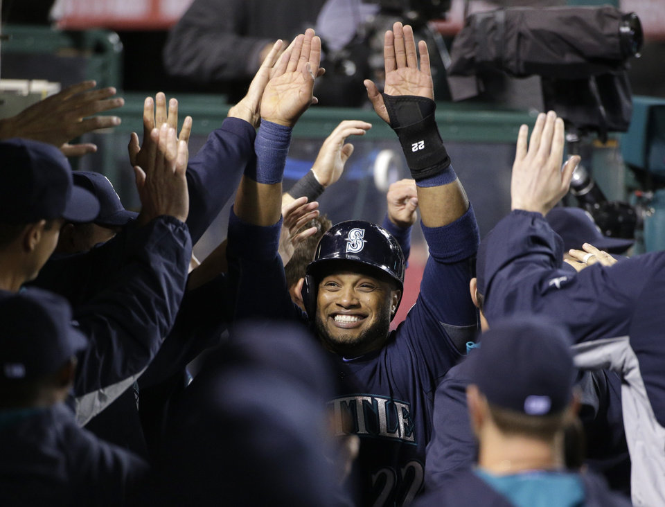 Photo - Seattle Mariners' Robinson Cano, center, is greeted by teammates after scoring on a double hit by Justin Smoak during the third inning of a baseball game against the Los Angeles Angels on Tuesday, April 1, 2014, in Anaheim, Calif. (AP Photo/Jae C. Hong)