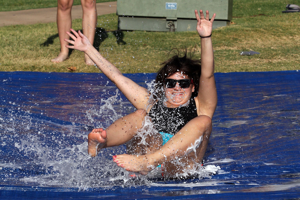 Photo - Jessica Kobriger, from Bartlesville, slides across the water at activities for University of Central Oklahoma students moving on campus in Edmond. PHOTO BY HUGH SCOTT, FOR THE OKLAHOMAN  HUGH SCOTT - FOR THE OKLAHOMAN