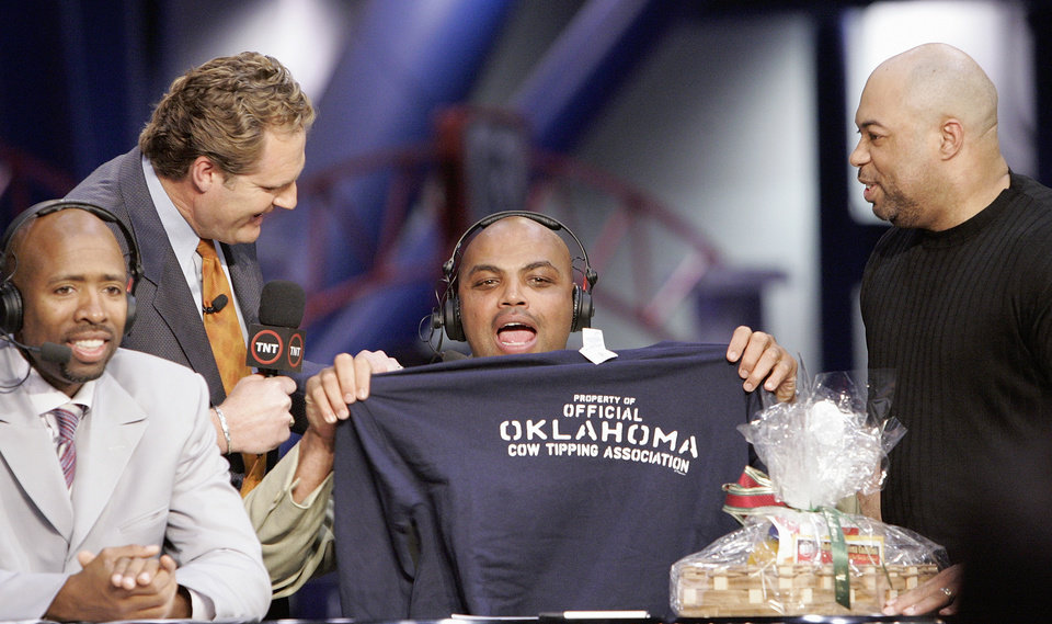 "Photo -  Charles Barkley holds up an ""Oklahoma Cow Tipping Association"" shirt presented to him by KWTV anchor Kelly Ogle, left, with microphone, and news director Blaise Labbe, right, (cq BLAISE LABBE) on the set of TNT's Inside the NBA at the NBA Jam Session, part of the NBA All-Star events in Houston, Texas, Febraury 16, 2006. Also pictured at right is TNT's Kenny Smith. Barkley has agreed to take up the challenge of Ogle and Labbe to visit Oklahoma. By Nate Billings, The Oklahoman."