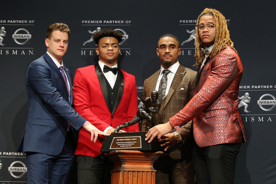 Photo - Dec 14, 2019; New York, NY, USA; Heisman finalists LSU Tigers quarterback Joe Burrow (left to right) and Ohio State Buckeyes quarterback Justin Fields and Oklahoma Sooners quarterback Jalen Hurts and Ohio State Buckeyes defensive end Chase Young pose for photos with the Heisman Trophy during a pre-ceremony press conference at the New York Marriott Marquis. Mandatory Credit: Brad Penner-USA TODAY Sports