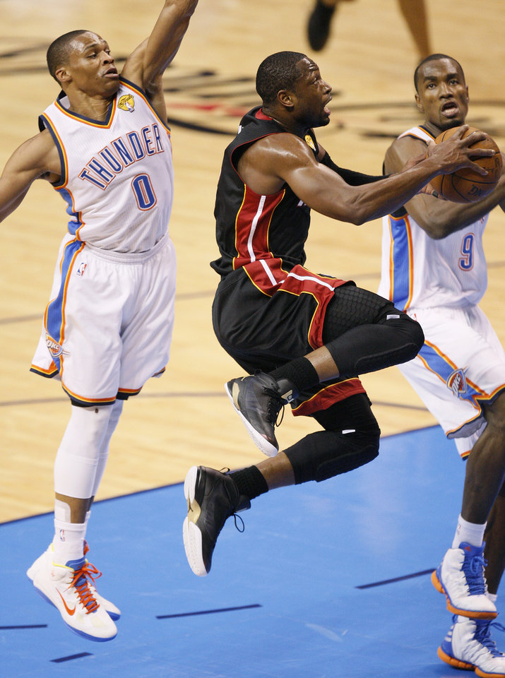 Photo - Miami's Dwyane Wade (3) goes to the basket between Oklahoma City's Russell Westbrook (0) and Oklahoma City's Serge Ibaka (9) during Game 2 of the NBA Finals between the Oklahoma City Thunder and the Miami Heat at Chesapeake Energy Arena in Oklahoma City, Thursday, June 14, 2012. Photo by Nate Billings, The Oklahoman