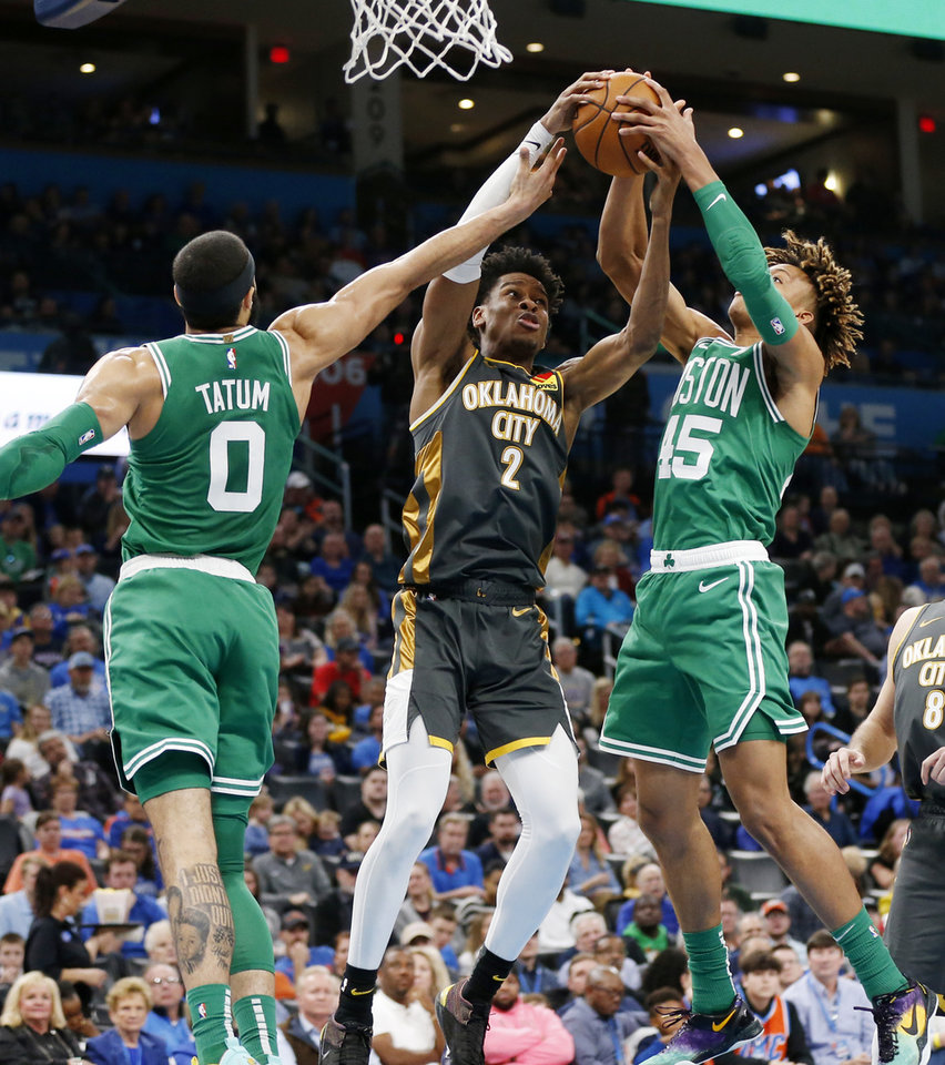 Photo - Oklahoma City's Shai Gilgeous-Alexander (2) grabs a rebound between Boston's Jayson Tatum (0), left, and Romeo Langford (45) in the second quarter during an NBA basketball game between the Oklahoma City Thunder and the Boston Celtics at Chesapeake Energy Arena in Oklahoma City, Sunday, Feb. 9, 2020. [Nate Billings/The Oklahoman]