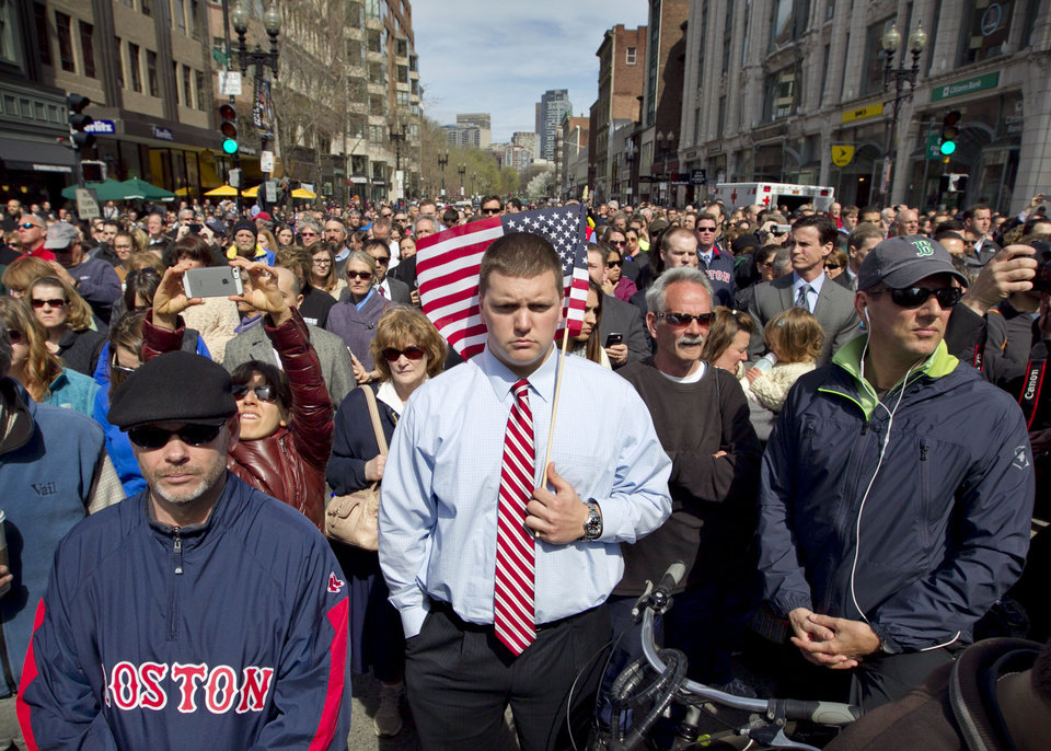 Photo - A moment of silence in honor of the victims of the Boston Marathon bombing is observed on Boylston Street near the race finish line, exactly one week after the tragedy, Monday, April 22, 2013, in Boston, Mass. (AP Photo/Robert F. Bukaty)