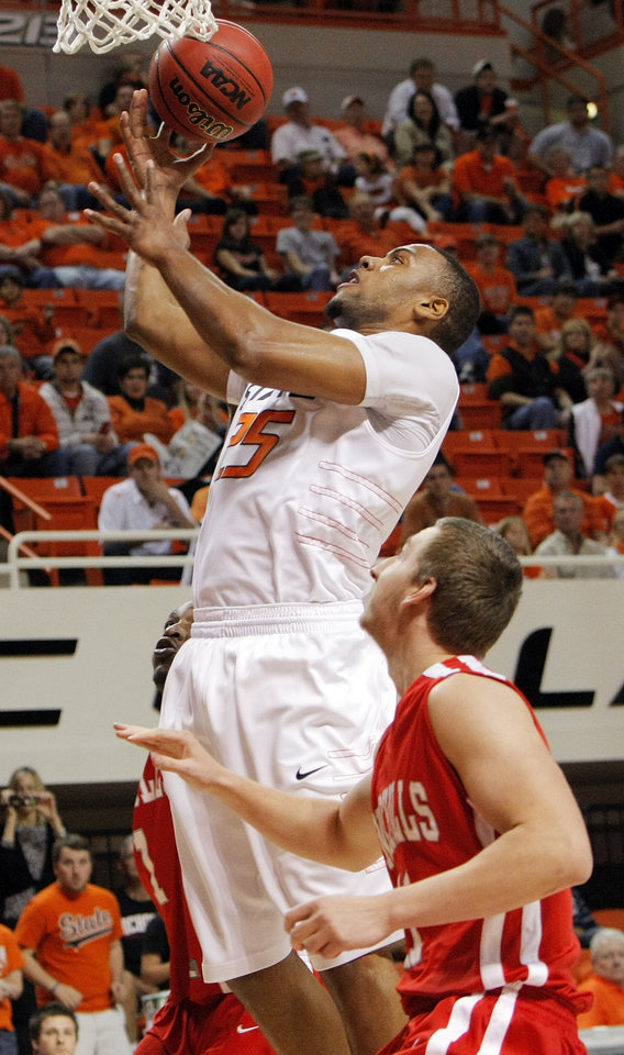 Photo - OSU's Darrell Williams (25) takes a shot in front of Chris Talkington (11) of Nicholls State in the first half during the men's college basketball game between Nicholls State University and Oklahoma State University at Gallagher-Iba Arena in Stillwater, Okla., Saturday, Nov. 21, 2010. Photo by Nate Billings, The Oklahoman