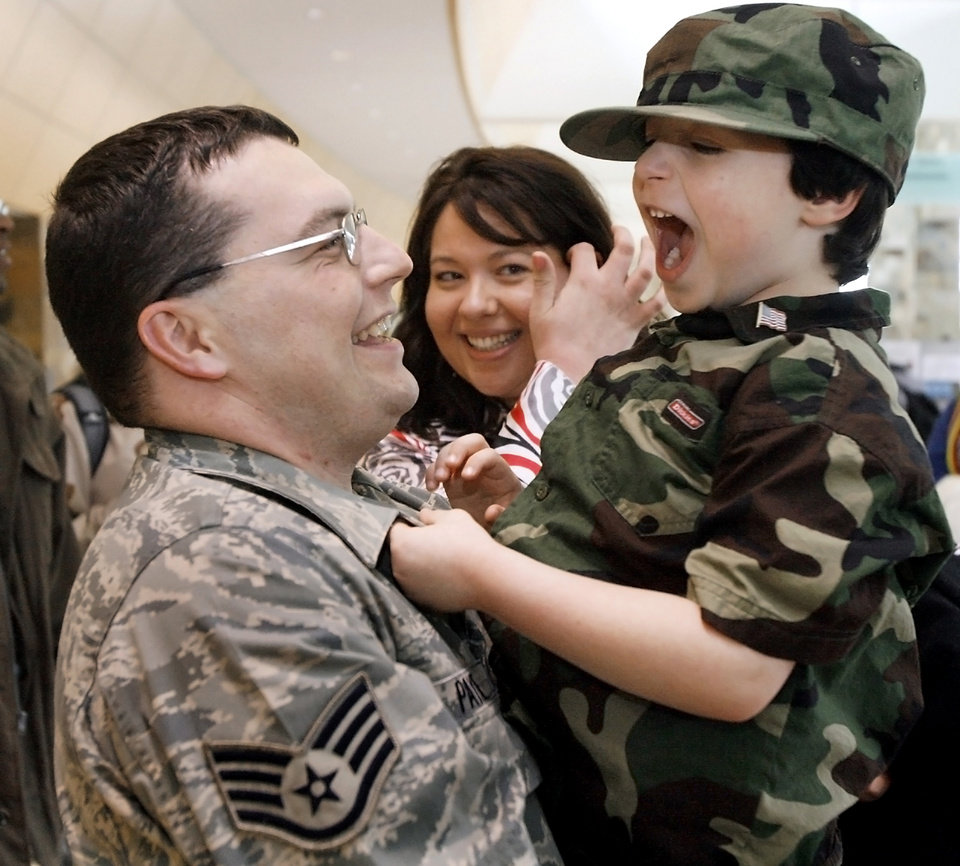 Photo - SECOND PLACE, GENERAL NEWS: Jacob Payne, 4, reacts as he is picked up by his father SSG James Payne while his mother Nicole looks on during the return of Tinker Air Force Base's 34th Combat Communications Squadron from a tour in Iraq at Will Rogers World Airport on Monday, Jan. 21, 2008, in Oklahoma City, Okla.   BY CHRIS LANDSBERGER, THE OKLAHOMAN
