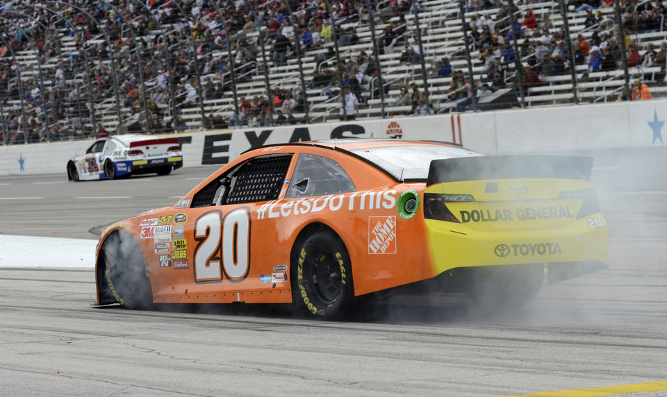 Photo - Matt Kenseth (20) locks up his brakes as he enters pit row during the NASCAR Sprint Cup series auto race at Texas Motor Speedway in Fort Worth, Texas, Sunday, Nov. 3, 2013. (AP Photo/Larry Papke)