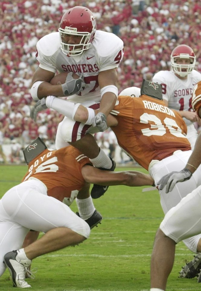DALLAS, Saturday,10/11/2003: University of Oklahoma vs. University  of Texas college football at Cotton Bowl.   OU's Renaldo Works leaps over UT Reed Boyd (45) and Brian Robinson. Staff photo by Jim Beckel.