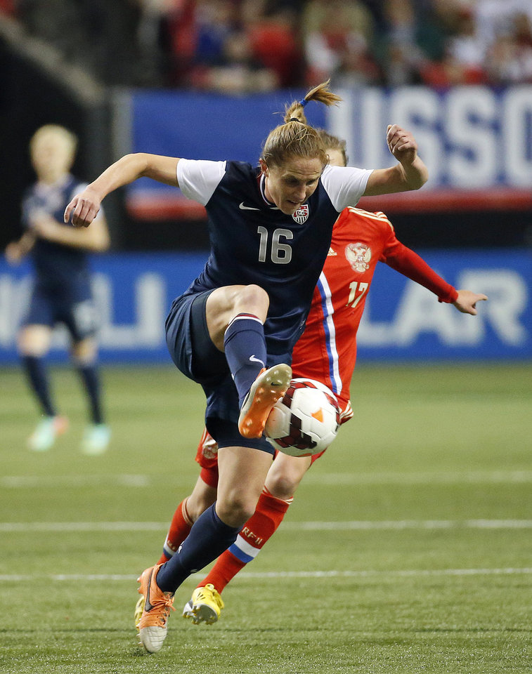 Photo - United States' Rachel Van Hollebeke (16) runs down the ball in the first half of an exhibition soccer match against Russia on Thursday, Feb. 13, 2014, in Atlanta. (AP Photo/John Bazemore)