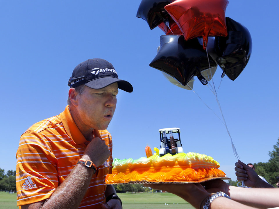 Photo - Scott Verplank blows out the candles on his 50th birthday cake presented to him by the USGA during practice rounds for the U.S. Senior Open golf tournament at Oak Tree National in Edmond, Okla. on Wednesday, July 9, 2014. Photo by Chris Landsberger, The Oklahoman