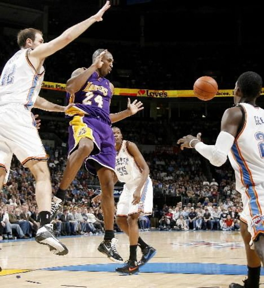 Kobe Bryant of the Lakers passes the ball between Oklahoma City's Nenad Krstic, left, Kevin  Durant and Jeff  Green during the NBA basketball game between the Los Angeles Lakers and the Oklahoma City Thunder at the Ford Center, Tuesday, Feb. 24, 2009. The Thunder lost 107-93. PHOTO BY BRYAN TERRY