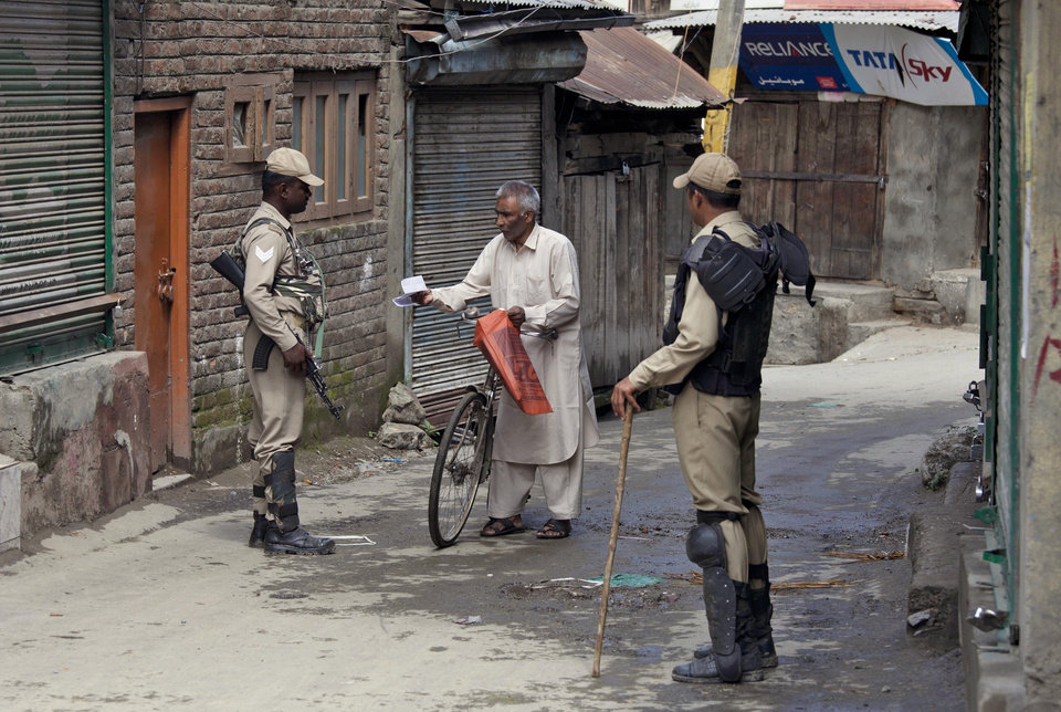 Photo - An Indian paramilitary soldier checks medical prescription papers of a man as they question him during restrictions in Srinagar, India, Friday, July 4, 2014. Shops, businesses and schools are shut in Indian-controlled Kashmir after separatist groups opposed to Indian rule announced a strike to protest a visit by the country's Prime Minister Narendra Modi. Modi is on his first official visit to the disputed Himalayan region and is expected to inaugurate a railway line and a power station, and also review security and development. (AP Photo/Dar Yasin)